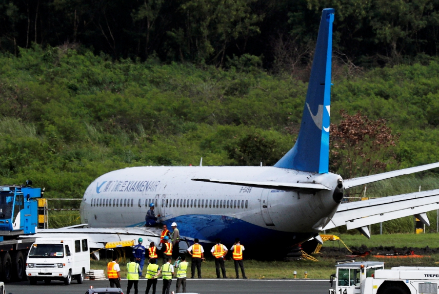 Workers try to remove a Xiamen Air Boeing 737-800 from the tarmac after it skidded off at the runway of Ninoy Aquino International airport in Paranaque, Metro Manila