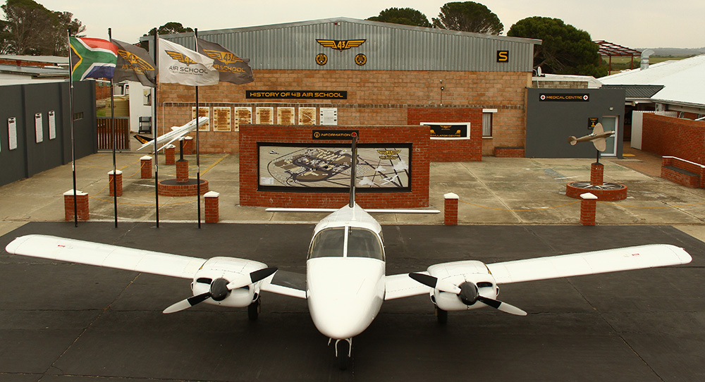 Piper twin positioned in front of the 43 Air School simulator centre